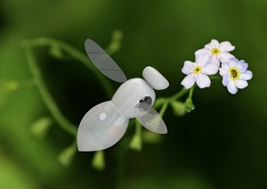 a miniature hi-tech looking flying robot flying around a flower